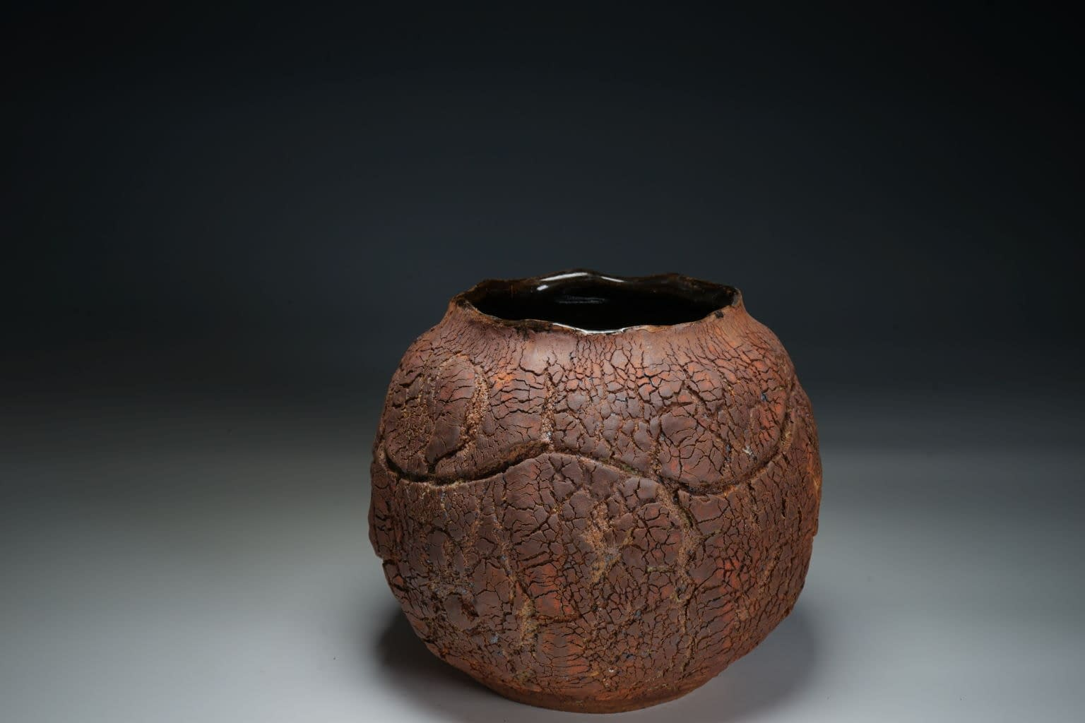 Rich dark moon vase form with heavy earth texture.