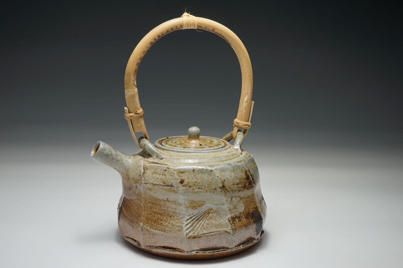 Wood salt fired teapot, cut sided surface. Heavy salt-glazed surface with sea shell indentation.
